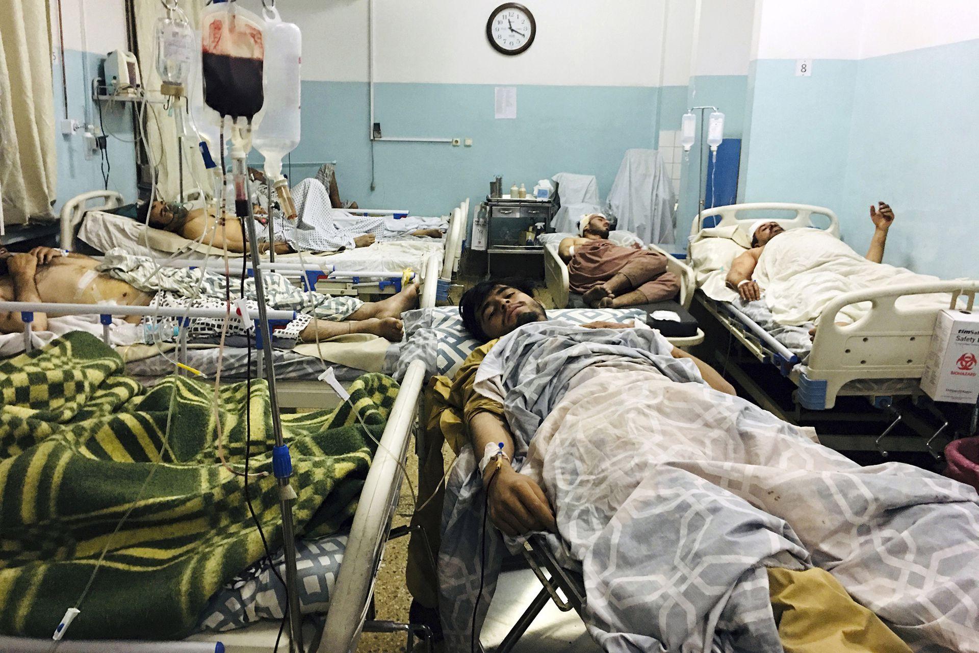 Afganos heridos yacen en una cama en un hospital después de una explosión mortal fuera del aeropuerto de Kabul, Afganistán.