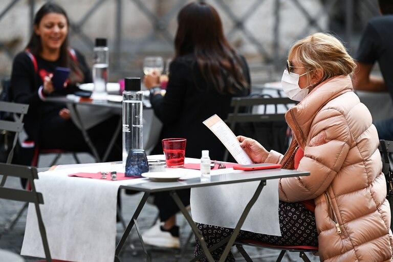 Una mujer lee un menú mientras se sienta en la terraza de un restaurante en el centro de Roma, el 25 de octubre de 2020, mientras el país enfrenta una segunda ola de infecciones por Covid-19