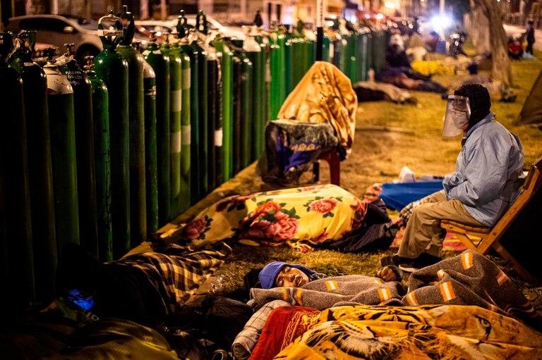 Familiares de pacientes con Covid-19 esperan durante la noche para realizar la recarga de los tubos de oxígeno, en Callao, Perú