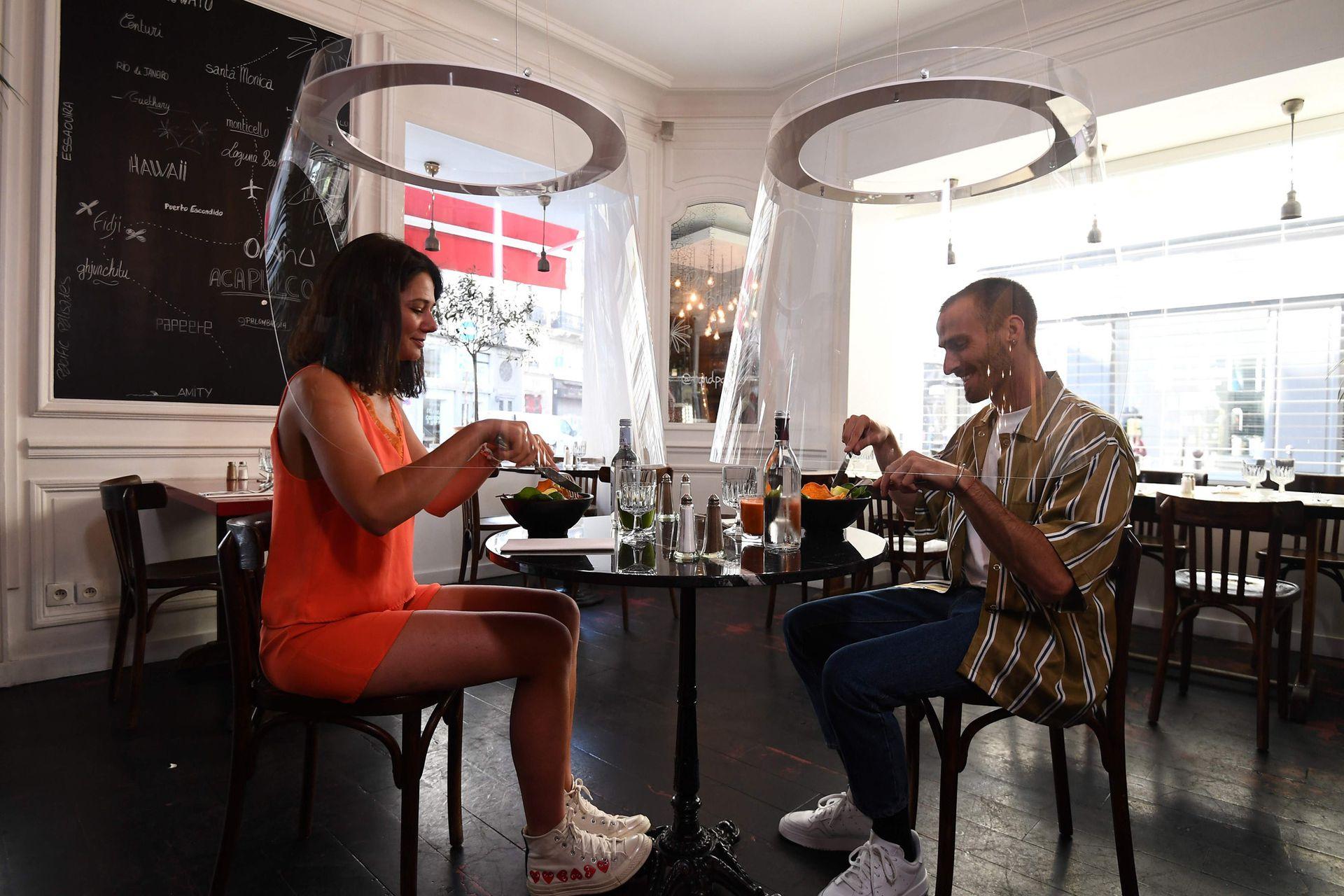 Una pareja almuerza bajo un novedoso método de protección en París
