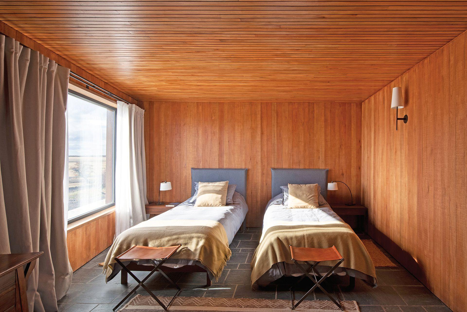 Otra habitación doble, en este caso ambientada con mesas de luz en madera con cajones telescópicos (Net Muebles), respaldos forrados, banquetas de cuero al pie de las camas (Paul French Gallery) y alfombra modelo 'Tejido Indio'.