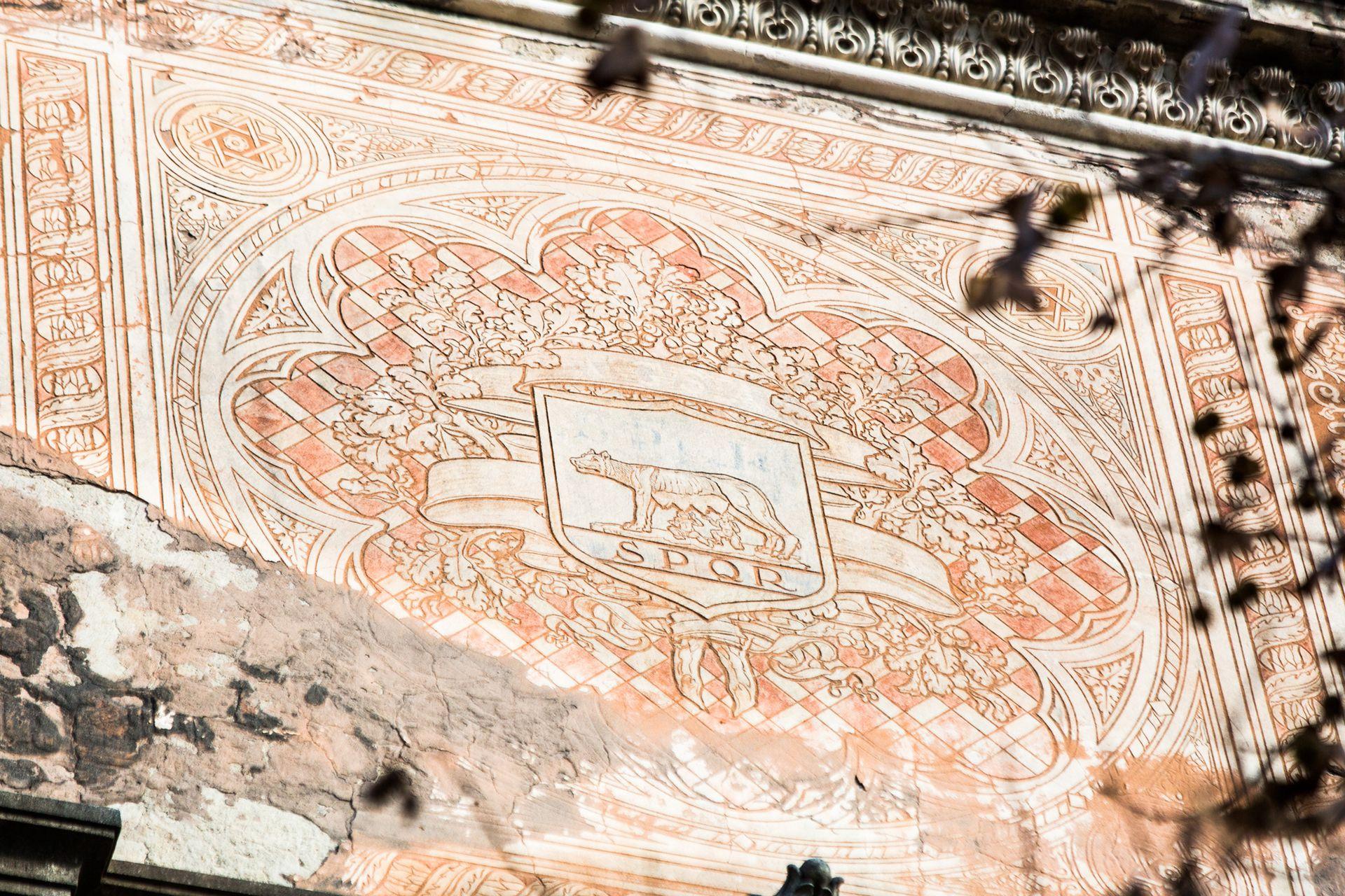 La loba romana y la sigla SPQR (Senatus Populus Que Romanus) en el frente del edificio.