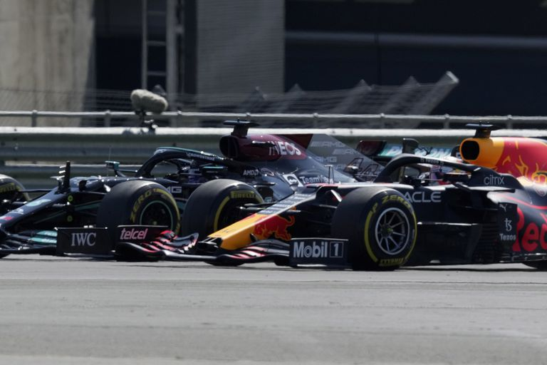 El británico Lewis Hamilton, izquierda, de Mercedes, y el holandés Max Verstappen, de Red Bull, toman una curva mientras pelean por la punta al inicio del Gran Premio Británico de la Fórmula Uno, en el circuito de Silverstone, Inglaterra, el domingo 18 de julio de 2021. (AP Foto/Jon Super)