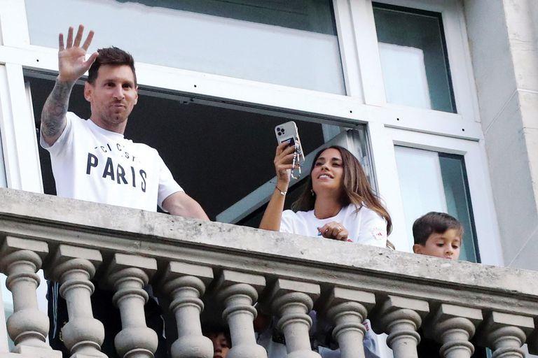 Leo, Anto y Thiago saludan a los fans desde una de las suites presidenciales del hotel. Ella captura el momento con su teléfono.