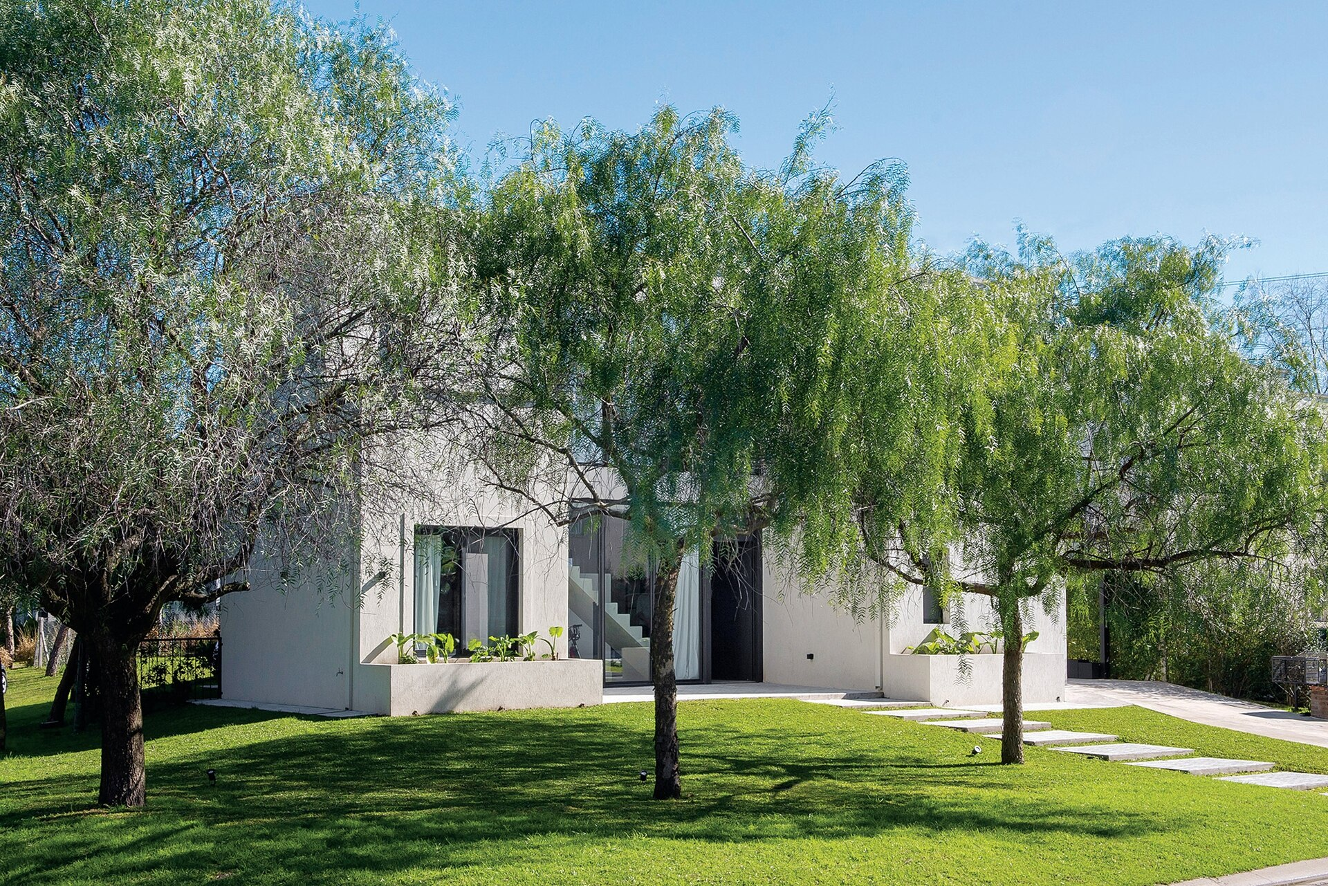 Un jardín con árboles da la bienvenida a la casa.