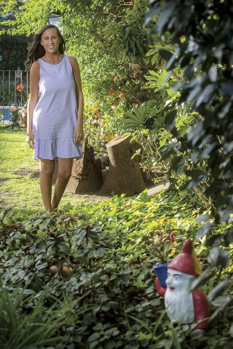 """Estefanía posa en el jardín de su casa de Vicente López. A su alrededor se puede ver la curiosa colección de enanos de jardín que atesora su marido. """"Tiene alrededor de cuarenta"""", dice."""