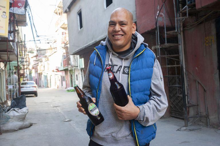 Osvaldo Salazar muestra orgulloso su cerveza en el Barrio 31