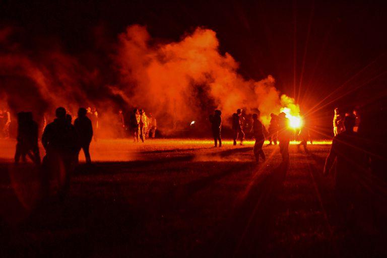 Jóvenes en un campo durante enfrentamientos con la policía mientras los agentes buscaban disolver una fiesta rave no autorizada cerca de Redon, Francia, la noche del viernes 18 de junio de 2021. (AP Foto)