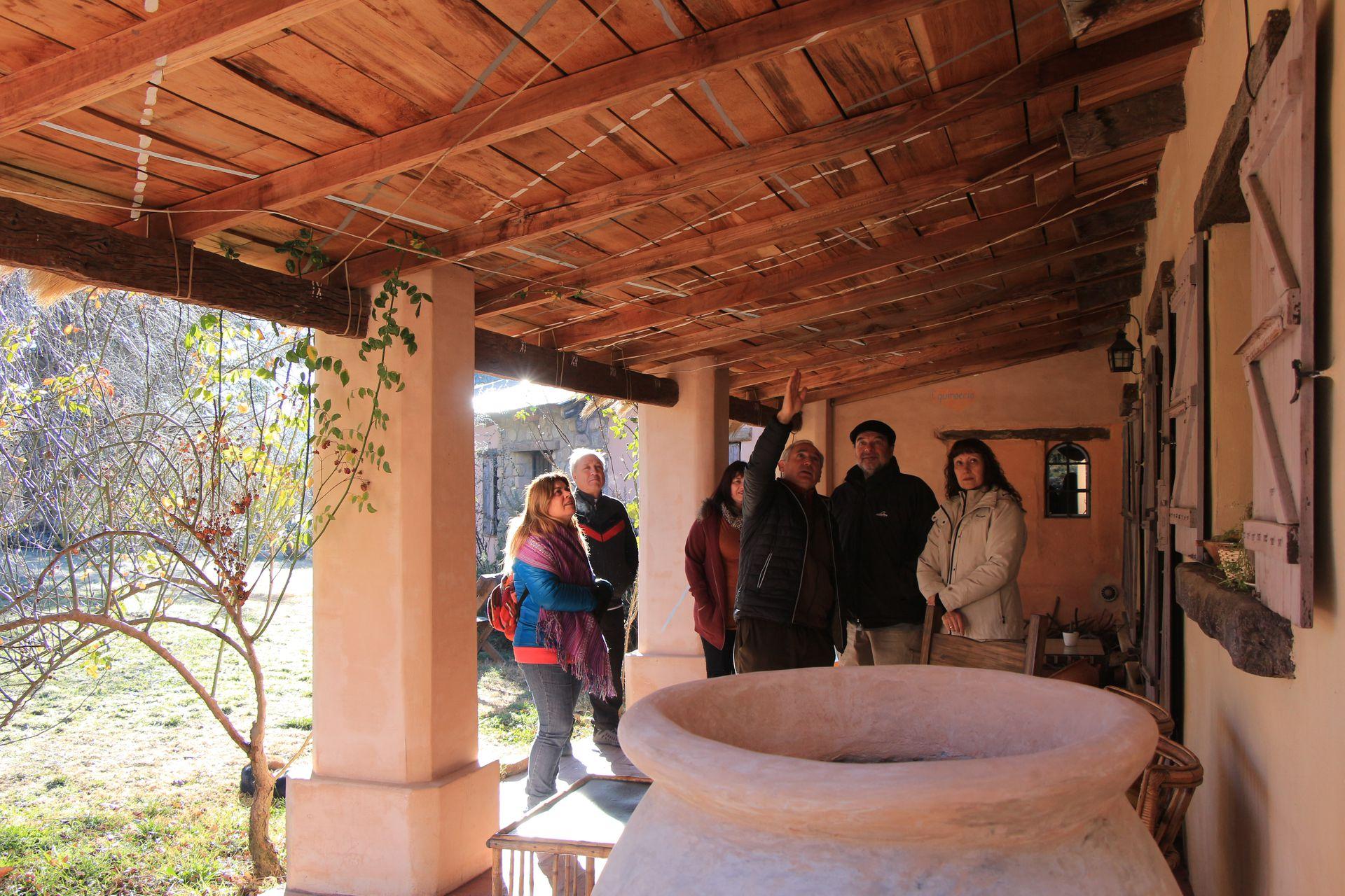 Juan les muestra a los huéspedes el reloj solar que él diseño sobre la galería.