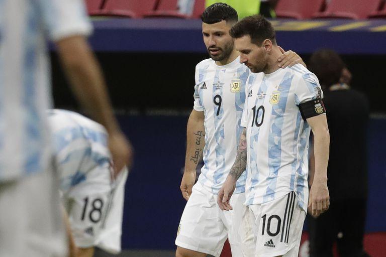 Sergio Agüero de rgentina, centro, abraza a su compañero de equipo Lionel Messi durante un partido de fútbol de la Copa América contra Paraguay en el estadio Nacional de Brasilia, Brasil, el lunes 21 de junio de 2021.