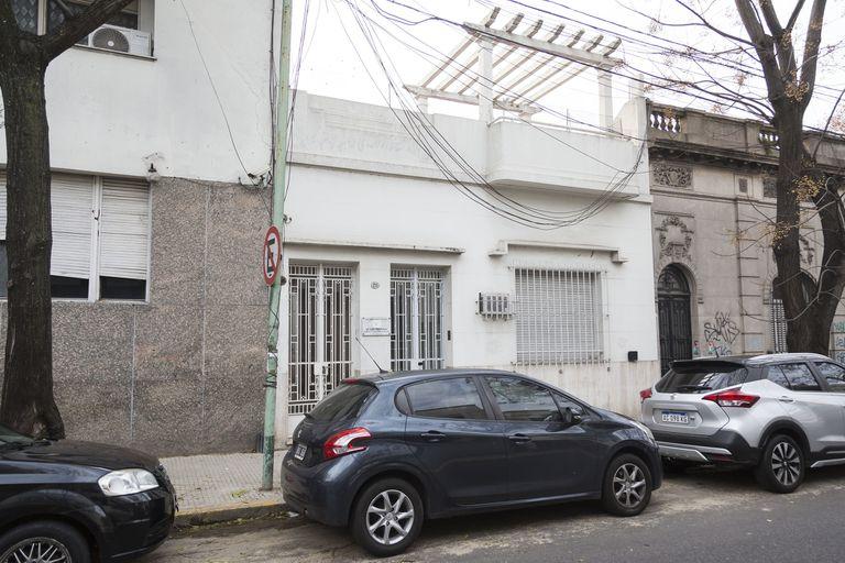 La fachada de la casa se destaca por sus dos puertas cubiertas con rejas blancas con dibujos geométricos simples