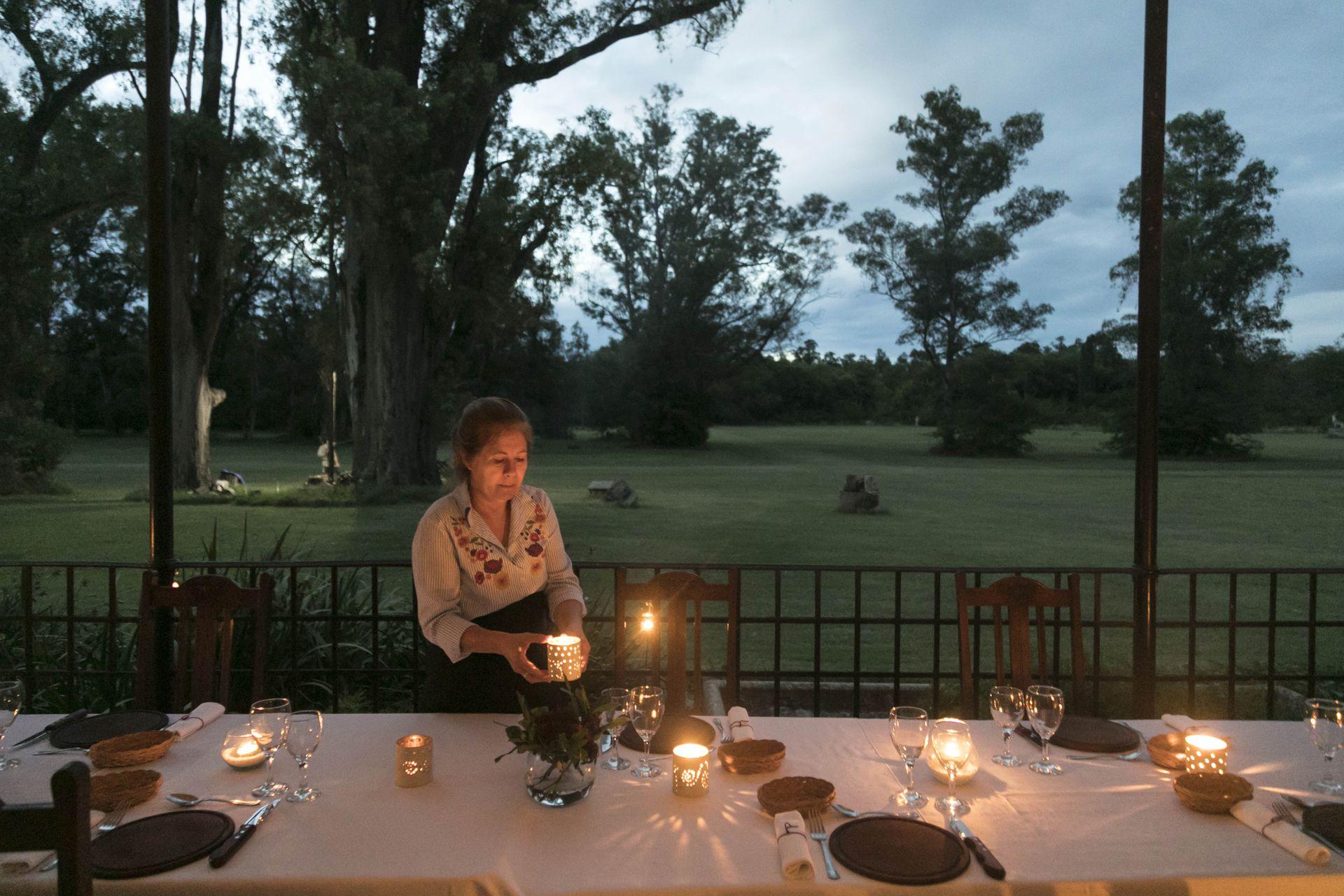 A la luz de las velas, la mesa servida en la galería con vista al extenso parque.