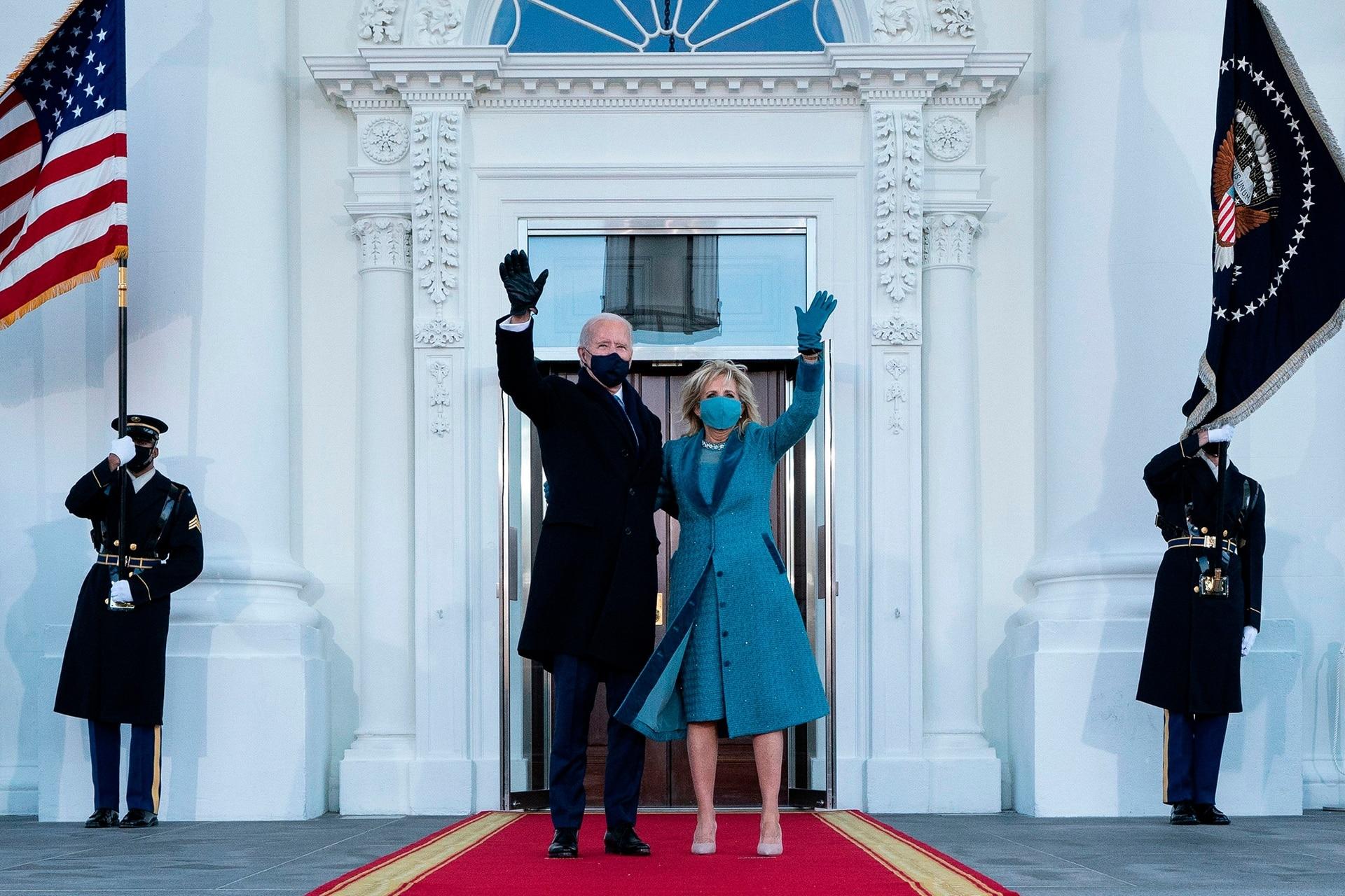 El presidente estadounidense Joe Biden y la primera dama Jill Biden saludan a su llegada a la Casa Blanca en Washington