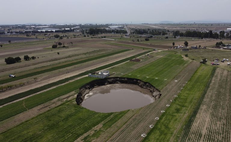 Un socavón con agua en el fondo continúa creciendo en un campo agrícola en Zacatepec, en las afueras del estado de Puebla, México, el martes 1 de junio de 2021. (AP Foto/Pablo Spencer)