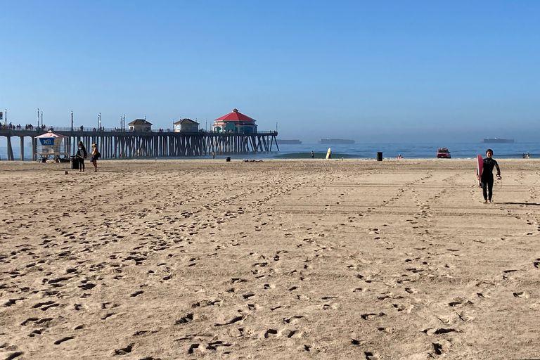 Surfistas salen del agua en una playa de Huntington Beach, California, el 10 de octubre de 2021. La playa, que se cerró hace más de una semana debido a una fuga en un oleoducto submarino reabrió el 11 de octubre. (AP Foto/Amy Taxin)