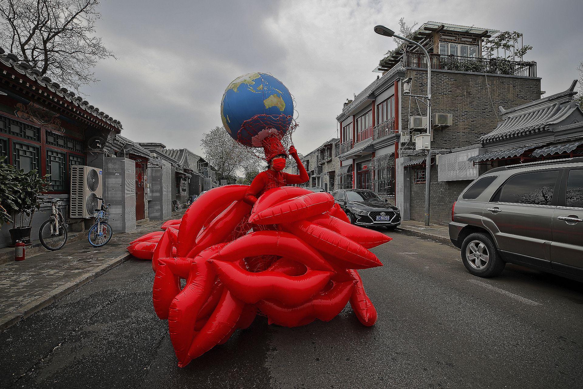 """La artista y activista ambiental china Kong Ning presenta su última colección de vestidos con el tema """"Besa la Tierra"""" en una calle en apoyo al Día de la Tierra en Pekín"""