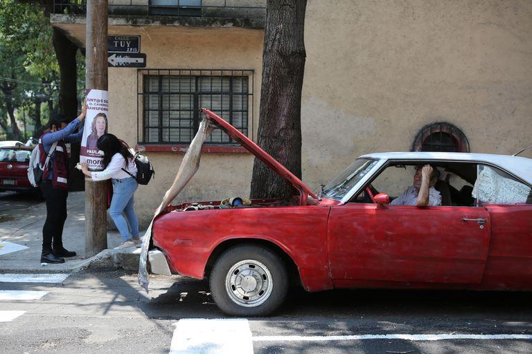 Simpatizantes de la candidata a la alcaldía del partido gobernante Morena, Paula Soto, colocan un cartel en un poste eléctrico en el último día de campaña previo a las elecciones intermedias del 6 de junio, en la Ciudad de México, el sábado 29 de mayo de 2021. (AP Foto/Ginnette Riquelme)