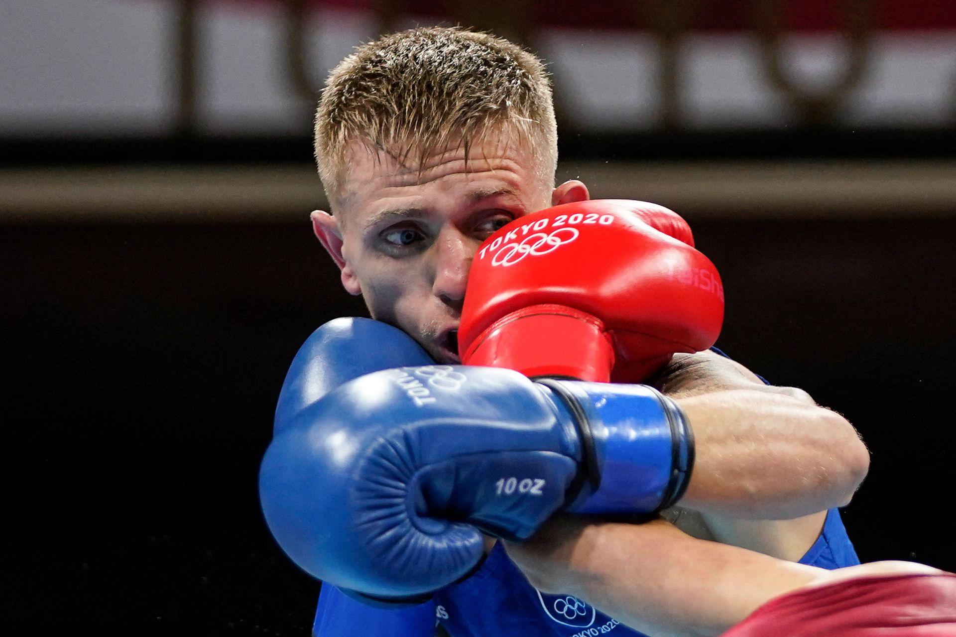 El irlandés Kurt Anthony Walker recibe un puñetazo del español José Quiles Brotons durante el combate de boxeo preliminar de plumas masculinas (52-57 kg) durante los Juegos Olímpicos de Tokio 2020 en el Kokugikan Arena de Tokio el 24 de julio de 2021.
