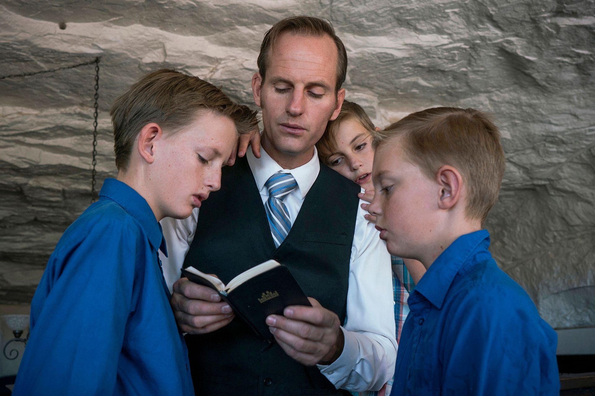 Enoch Foster y tres de sus hijos leen la Biblia mormona durante la iglesia dominical, que tiene lugar en una de las cuevas de la comunidad en Utah (2018)