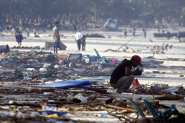Un hombre tailandés rodeado por el daño causado por un tsunami se agacha en la arena de la playa de Patong en Phuket, el 27 de diciembre de 2004.