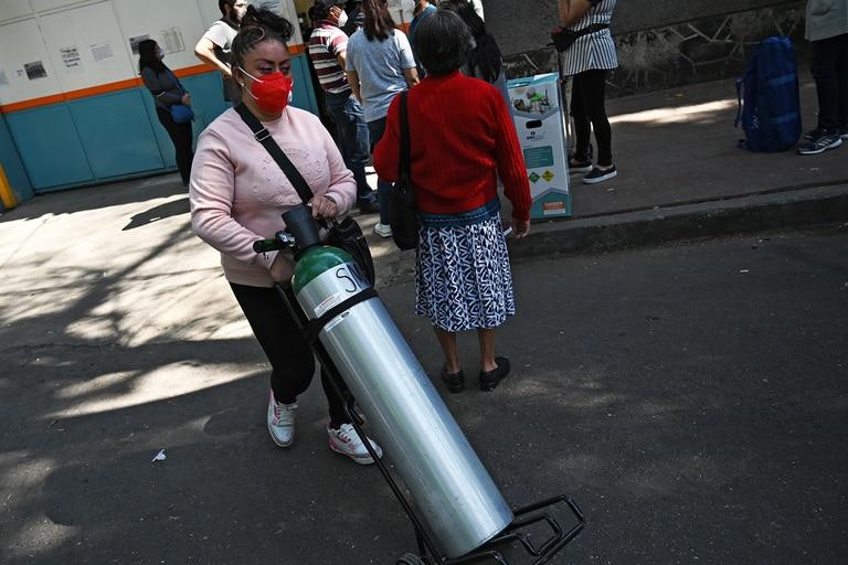Una mujer empuja un tanque de oxígeno junto a una cola de personas haciendo cola para rellenar el suyo en la empresa Infra Medica en la Ciudad de México, el 22 de enero de 2021