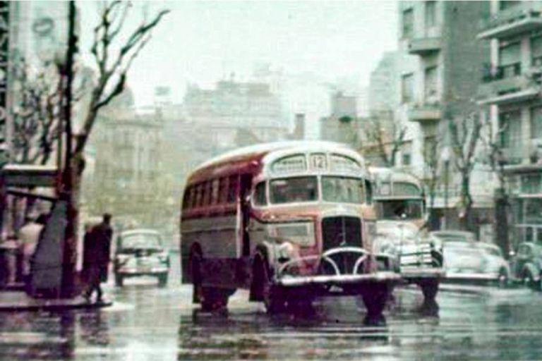 Dos colectivos de la línea 12 circulan por la Avenida Santa Fe en el cruce por Pueyrredón un día lluvioso del año 1960