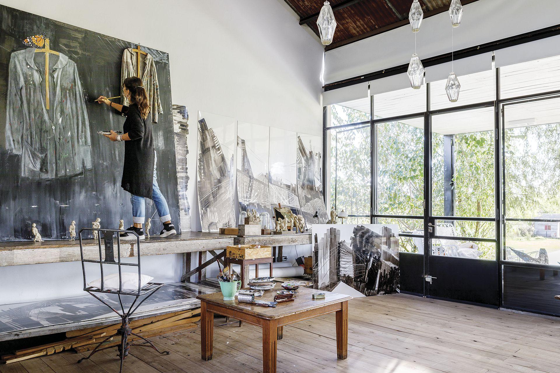 """Con fuertes superficies de madera donde puede trabajar sus obras más grandes, Berna armó su taller en el extremo del living. """"Pensé en un piso que pudiera manchar sin preocuparme"""", dice, contenta con su casa de uso absoluto."""