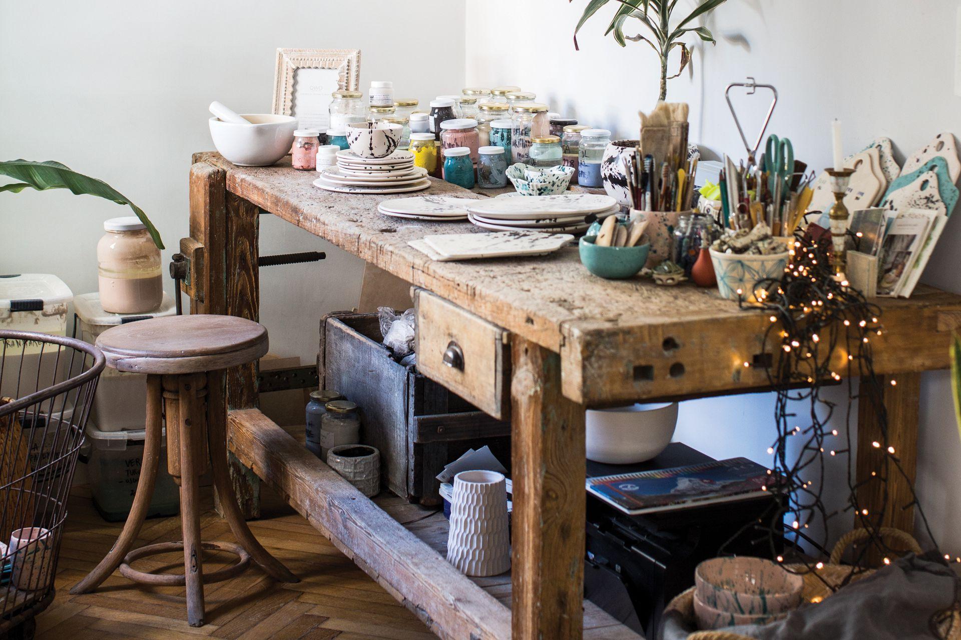En el taller, tanto la mesa de carpintero como el banco y el canasto de panadero son antigüedades encontradas en Tandil.