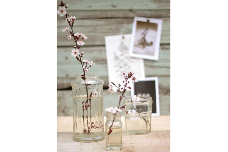 Las flores son iguales; lo que cambia es la composición, hecha con una variedad de frascos de dulce a los que se le quitaron las etiquetas. Todos transparentes, el conjunto hace que se destaquen sus distintos diseños.
