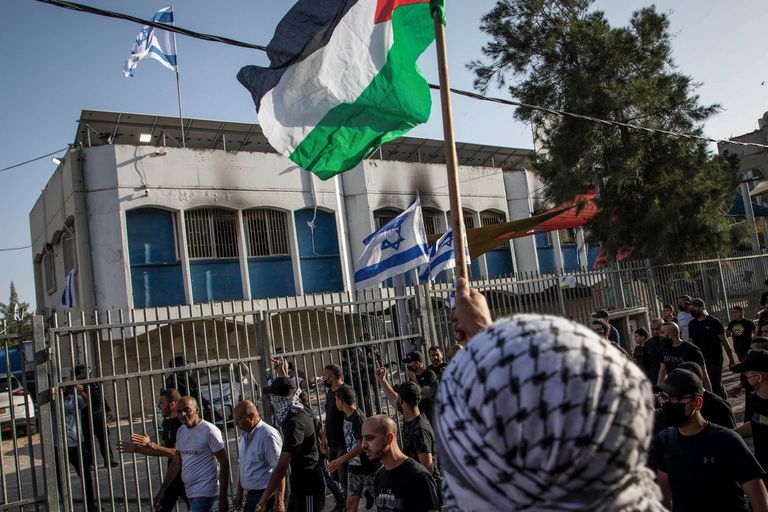 Árabes ondean banderas palestinas contra los israelíes en un edificio de la comunidad judía durante los nuevos disturbios en la ciudad de Lod.