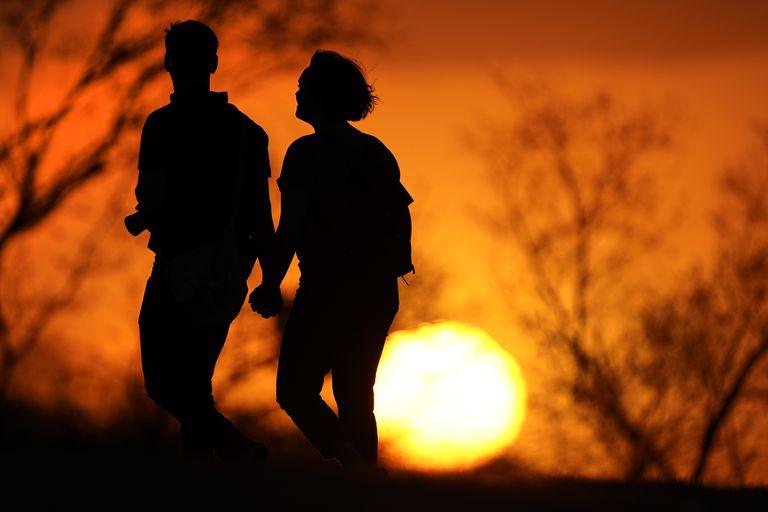 En esta imagen de archivo, tomada el 10 de marzo de 2021, una pareja camina por un parque al atardecer, en Kansas City, Missouri. (AP Foto/Charlie Riedel, archivo)