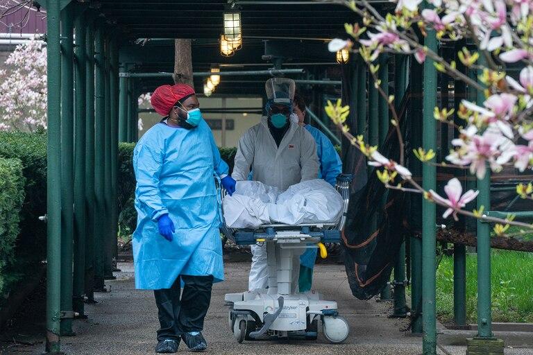 Los empleados del Kingsbrook Jewish Medical Center transportan a un paciente fallecido a un camión refrigerado el 8 de abril de 2020 en el distrito de Brooklyn de la ciudad de Nueva York