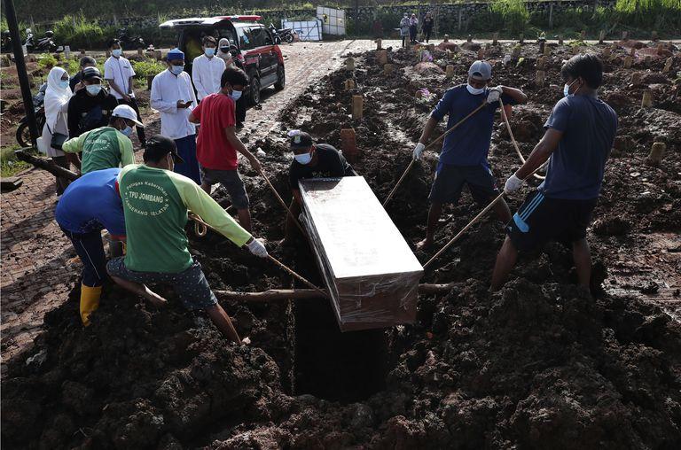 Unos trabajadores bajan un ataúd durante la inhumación de una víctima fatal de Covid-19, en una zona especial para esos cadáveres en el cementerio público de Jombang, el lunes 21 de junio de 2021 en Tangerang, en las afueras de Yakarta, Indonesia