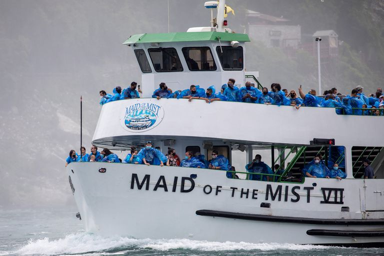 Asomados en la borda, los turistas que salieron desde el lado estadounidense se amontonan para obtener la mejor foto en el Niágara; los barcos ocupan el 50% de su capacidad por el coronavirus