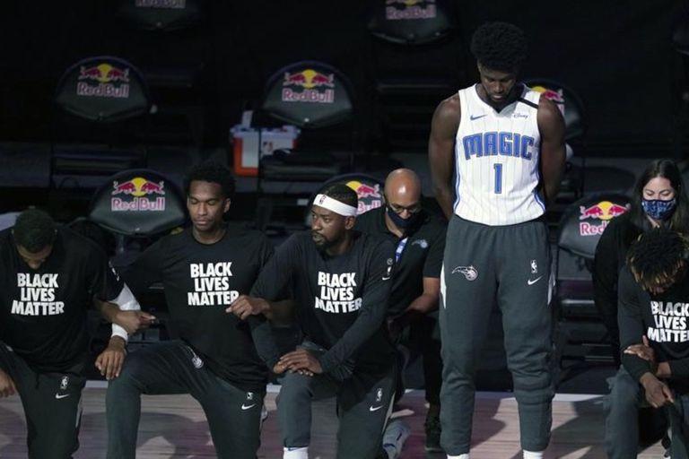 John Isaac, de Orlando Magic, sin la camiseta de Orlando Magic y parado, en medio de sus compañeros