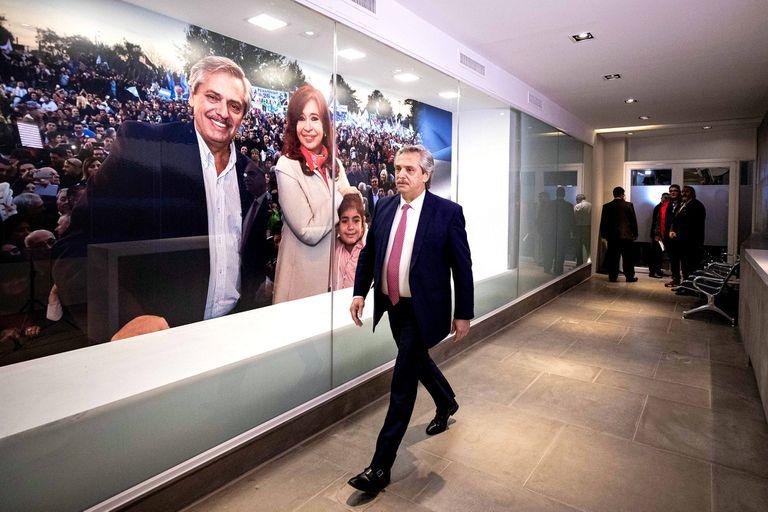 Alberto Fernández, ingresando al bunker. A su lado, el mural que lo muestra junto a Cristina Kirchner