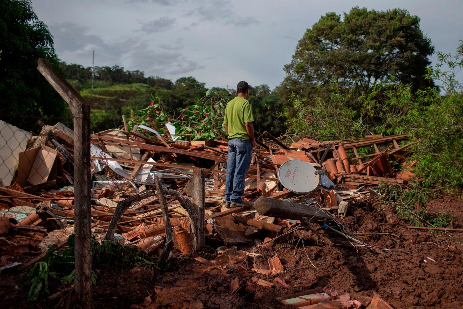 La gente de la comunidad del Parque da Cachoeira observa los escombros en el área afectada por el lodo un día después del derrumbe de una represa en una mina de mineral de hierro perteneciente a la gigante minera brasileña Vale, cerca de la ciudad de Brumadinho en el estado de Minas Gerias. sureste