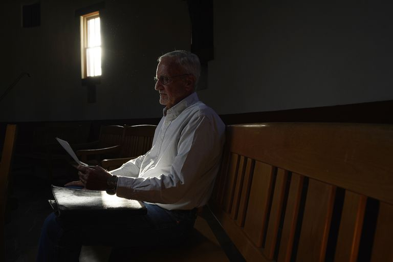 El reverendo John Fife III revisa viejas fotografías sobre su activismo en defensa de los migrantes el 17 de mayo del 2021 en Tucson, Arizona. (AP Photo/Ross D. Franklin)