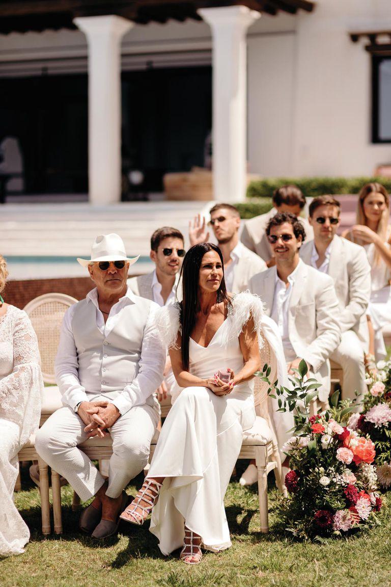 Fiel al dress code establecido para el gran día (total white), la mamá del novio, Carolina Baldini, impactó con un vestido con plumas en los hombros que complementó con sandalias plateadas.