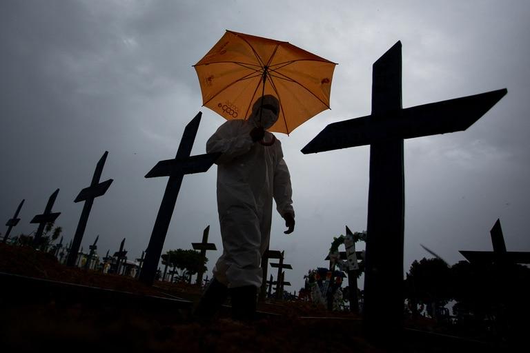 Un trabajador vestido con un traje protector y con un paraguas camina frente a las tumbas de las víctimas del Covid-19 en el cementerio de Nossa Senhora Aparecida, en Manaus