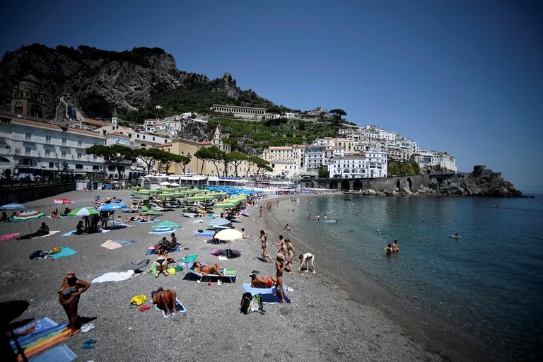 La fotografía, tomada el 2 de julio de 2020, muestra a turistas y residentes tomando sol y nadando en una playa de Amalfi en el sur de Italia