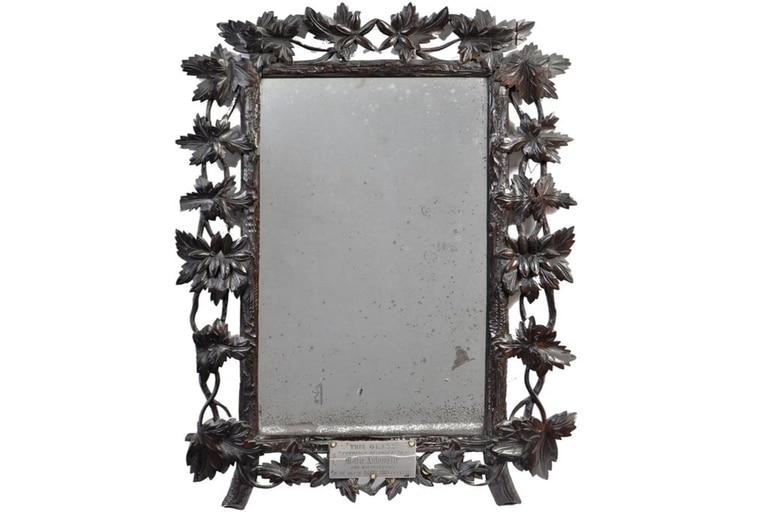 El espejo mide cincuenta por cuarenta centímetros y está rodeado por un marco de madera de nogal tallada con forma de enredadera