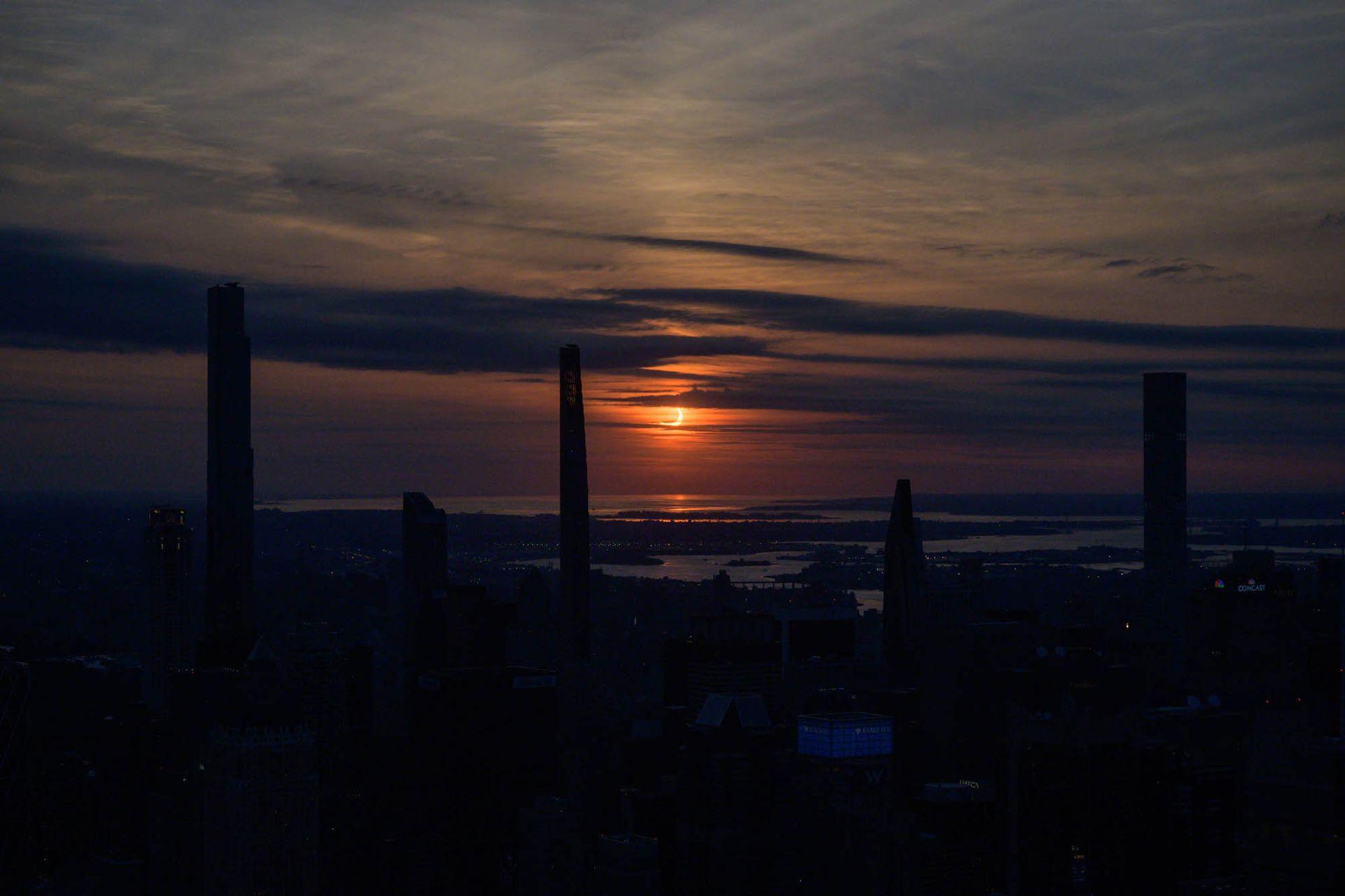 El eclipse solar parcial se eleva entre los edificios del horizonte de Manhattan desde el mirador Edge en Nueva York.