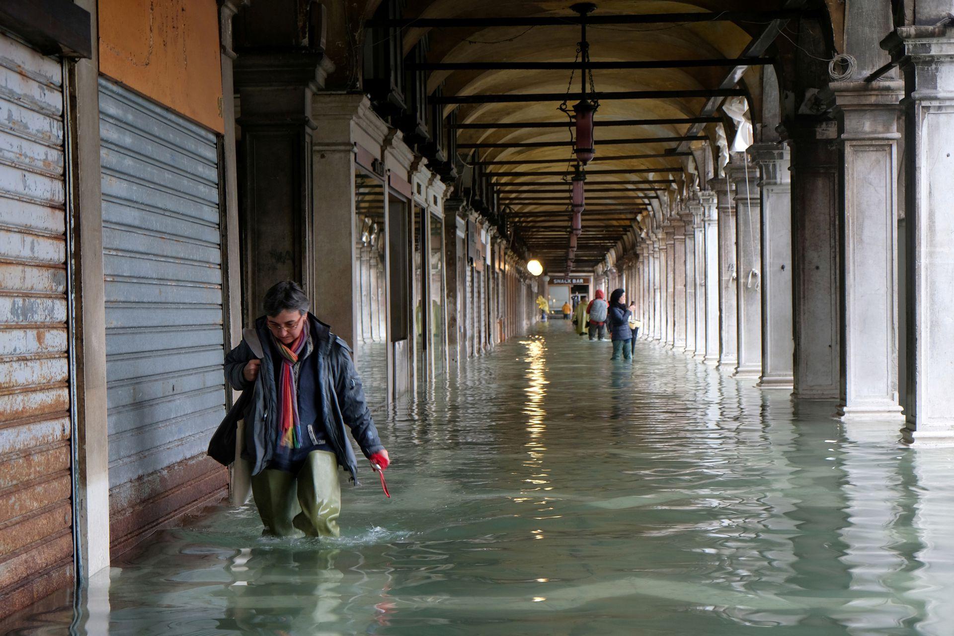 Una mujer camina por la inundación bajo las recovas de la plaza San Marcos.