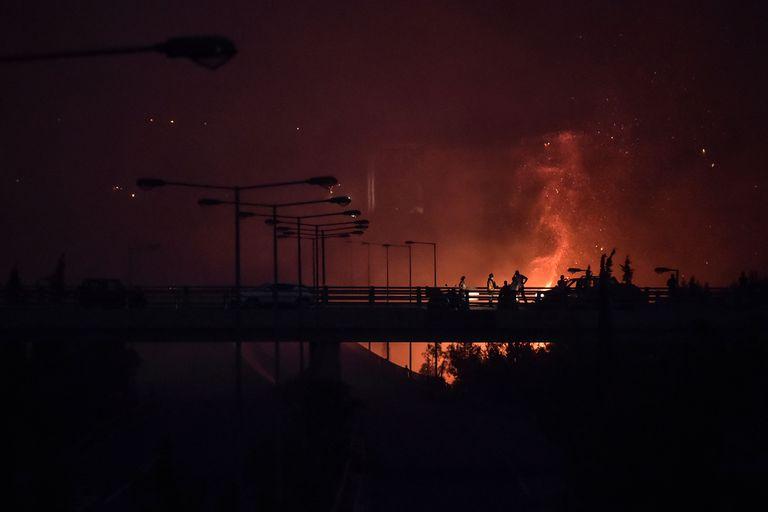 Un incendio bordea una autopista cercana a Atenas (Photo by LOUISA GOULIAMAKI / AFP)