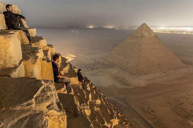 Los tres jóvenes fotógrafos rusos hacen una pausa en la cima de la pirámide de Keops para contemplar El Cairo de noche