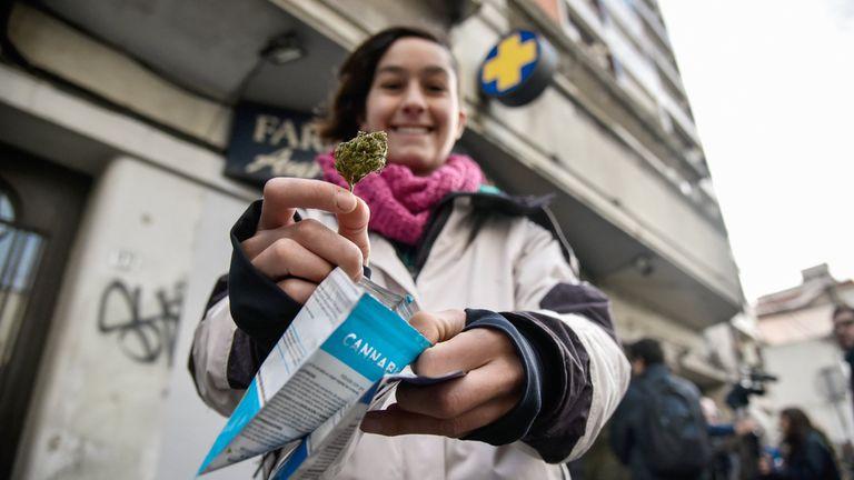 Una mujer muestra un paquete de marihuana comprado en una farmacia en Uruguay