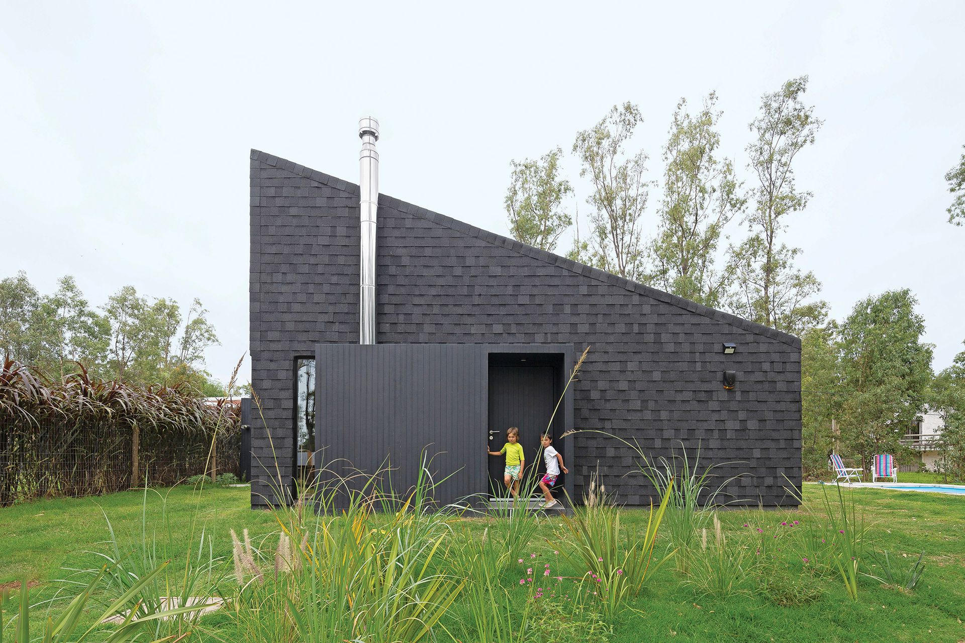 Las tejas asfálticas volumétricas (Iko), frecuentes en techados de construcciones en seco, revisten también el muro para conseguir el efecto de continuidad que caracteriza la obra.