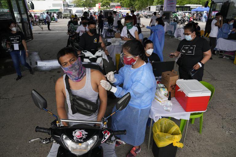 Un conductor de motocicleta recibe una dosis de la vacuna contra el COVID-19 desarrollada por la farmacéutica china Sinovac en un puesto de vacunación en Manila, Filipinas, el 22 de junio de 2021. (AP Foto/Aaron Favila)