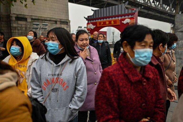 Turistas nacionales de la provincia de Henan con máscaras faciales visitan un área junto al río Yangtze en Wuhan el 20 de noviembre de 2020